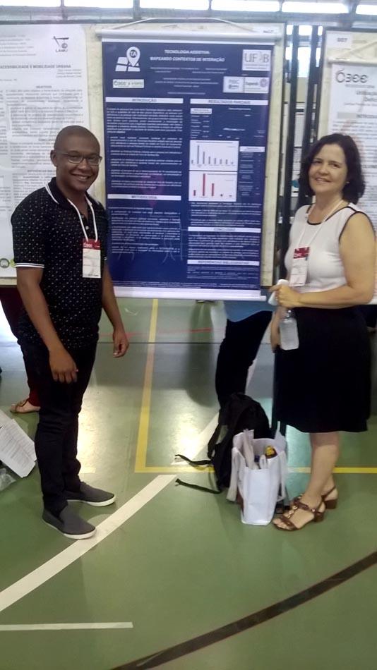 A Professora Nelma Galvão e o estudante Lucas Reis ao lado do poster com o segundo trabalho apresentado.