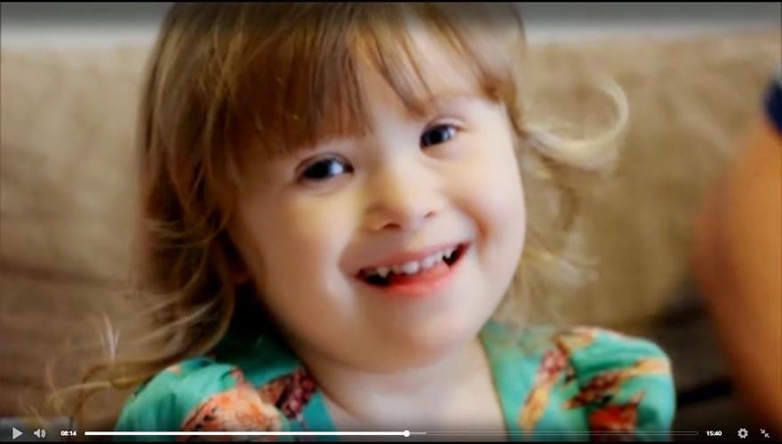 Imagem de uma criança com Síndrome de Down sorrindo