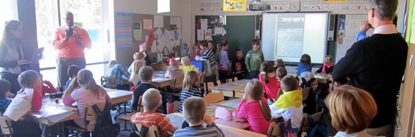 Foto de uma sala de aula com mesas, crianças e alguns adultos.