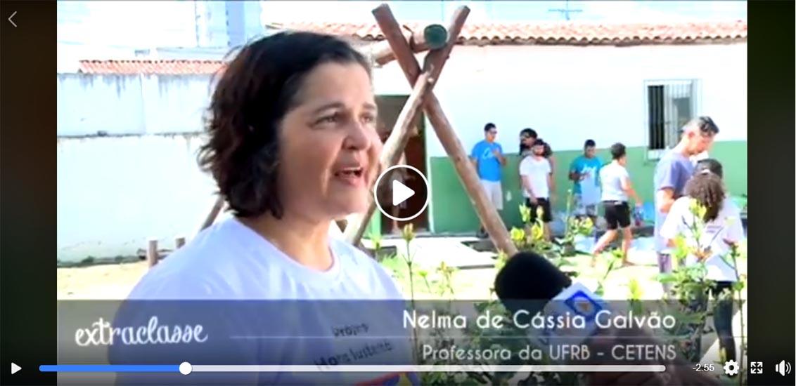A Professora Nelma Galvão sendo entrevistada com as atividades da horta acessível ao fundo