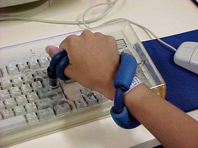 Foto: Aluno digitando, utilizando diferentes recursos de Tecnologia Assistiva (acervo pessoal)