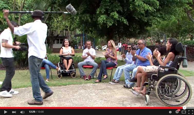Foto de um grupo de estudantes sentados em semicírculo, numa área arborizada, sendo filmados.