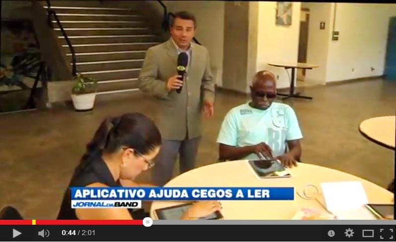 Reporter falando e alunos com deficiência visual usando o tablet