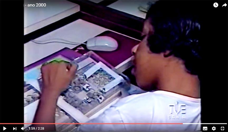 Imagem de um vídeo no qual aparece uma jovem utilizando um computador com o teclado adaptado com recursos de Tecnologia Assistiva